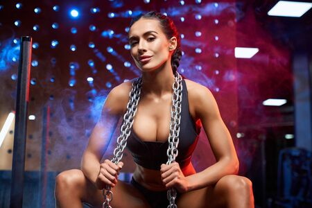 Front view of young smiling fitness woman in black sportswear with braids holding chains on neck. Athlete female with perfect body sitting in gym, looking at camera. Concept of sport, bodybuilding. 写真素材