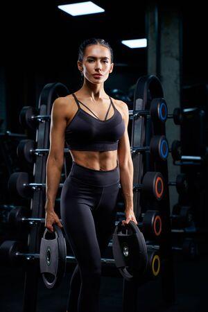 Portret van fitnessvrouw met vlechten poseren in de buurt van stand met sportuitrusting en gewichten te houden. Srtong vrouw met gespierd lichaam staande in de sportschool in donkere sfeer, camera kijken. Stockfoto