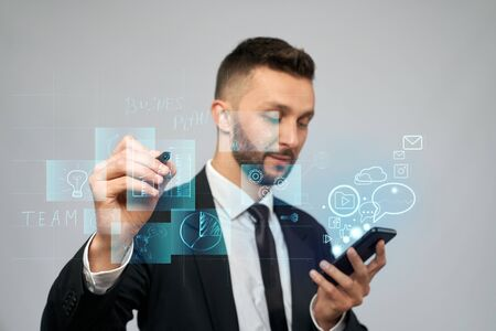 Front view of businessman in suit holding phone with virtual projection in office. Serious man clicking virtual button on digital tactile charts screen with stylus. Concept of gadgets, digitalization. Standard-Bild
