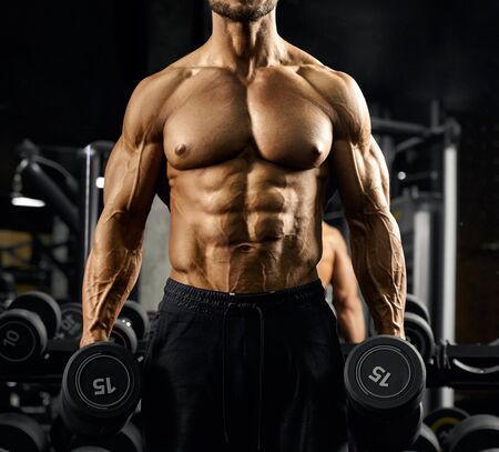Front view of shirtless incognito male bodybuilder holding dumbbells in arms. Close up of sportsman with perfect tensed muscular body posing in gym in dark atmosphere. Concept of bodybuilding.