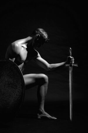 Side view of strong warrior standing on knee and looking down. Monochrome portrait of muscular athlete posing and holding sword and shield in black studio background. Cocept of warrior, strength.