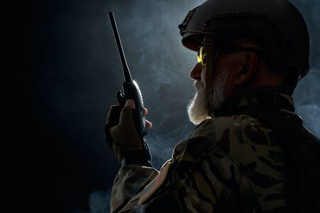 Side view of old military soldier in uniform holding portable radio station in smoke. Close up of male commander in camouflage uniform giving orders in dark atmosphere. Concept of army, military. 免版税图像 - 139558852
