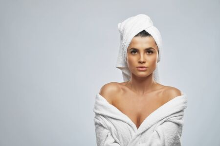 Front view of pretty female with towel on head and in bathrobe posing. Portrait of brunette woman with shoulders looking at camera, isolated on grey background. Beauty, skincare concept.