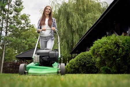 Front below view of pretty young smiling woman using lawn mower on backyard. Female gardener with long hair working in summer, cutting grass in backyard. Concept of gardening, work, nature. Archivio Fotografico