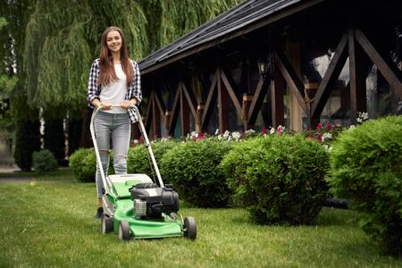 Front view of pretty young smiling woman using lawn mower on backyard, looking at camera. Female gardener working in summer, cutting grass in backyard. Concept of gardening, work, nature. Imagens