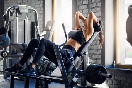 Side view of fit young brunette sportswoman in black sportswear sitting on simulator in gym and holding arms behing neck. Slim fitnesswoman training buttocks, doing gluteal bridge exercise.