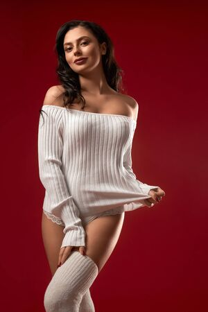 Portrait of fashionable smiling brunette woman posing in white sweater, knee socks and underwear. Front view of sensual girl touching clothes and looking at camera, isolated on red studio background.