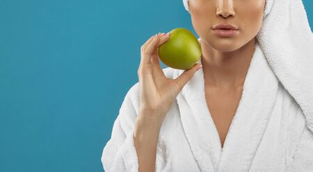 Crop of young caucasian woman wearing towel on head and white bathrobe, holding green apple. Incognito female with strong face posing on blue studio background. Concept of beauty.