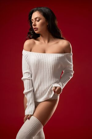 Portrait of fashionable brunette woman posing in white sweater, knee socks and underwear. Front view of sensual young girl with big neckline looking away, isolated on red studio background.