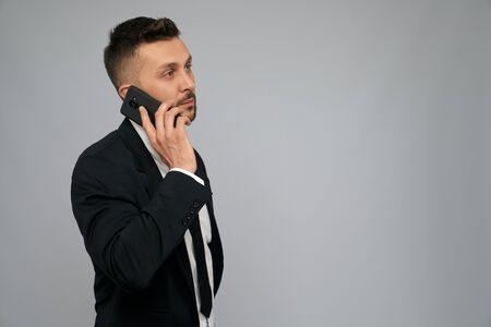 Side view of handsome brunette businessman in black formal suit talking on phone in office. Portrait of young serious bearded man working, negotiating, isolated on grey. Concept of gadgets, business.