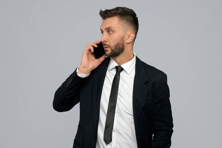 Front view of young brunette businessman in black formal suit talking on phone in office. Handsome serious bearded man working, negotiating, isolated on grey. Concept of gadgets, business.