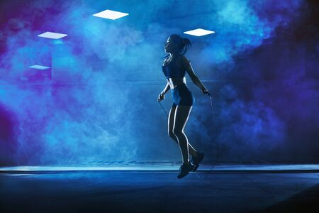 Side view of pretty female bodybuilder in sport suit with perfect body using skipping rope in gym. Young athletic woman jumping in hall, dark atmosphere with smoke and backlit. Concept of sport.