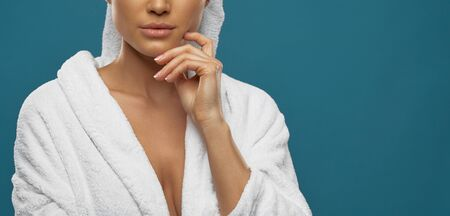 Front view of young slim female with towel on head and in bathrobe posing. Crop portrait of incognito caucasian woman touching chin, isolated on blue background. Beauty, skincare concept. 写真素材