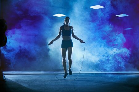 Front view of pretty female bodybuilder in sport suit with perfect body using skipping rope in gym. Young athletic woman jumping in hall, dark atmosphere with smoke and backlit. Concept of sport.