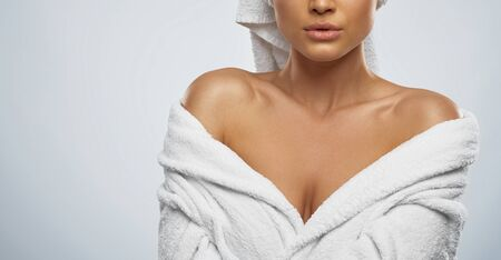 Front view of female with towel on head and in bathrobe posing. Crop portrait of incognito caucasian woman with naked shoulders, isolated on grey background. Beauty, skincare concept.