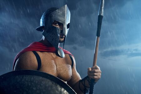 Portrait of spartan warrior standing outdoors with spear and shield in evening. Close up of muscular man in red cloak and helmet posing in bad cloudy rainy weather. Ancient sparta concept.