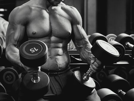 Front view of shirtless incognito male bodybuilder holding dumbbells in arms on thighs. Close up of sportsman with perfect body posing in gym in dark atmosphere, monochrome. Concept of bodybuilding.