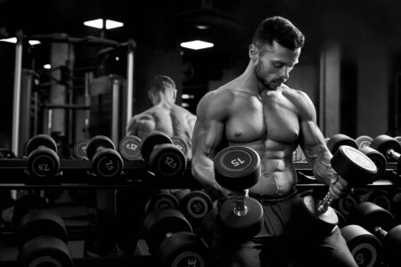 Front view of shirtless male bodybuilder holding weights in arms on thighs. Sportsman with perfect muscular body having rest after training in gym, sitting on dumbbells. Concept of bodybuilding. 写真素材