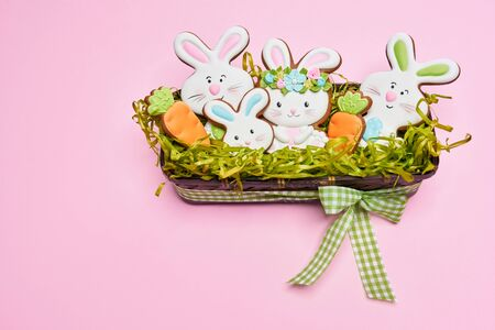 From above view of glazed cookies in shape of lovely bunnies and carrots lying in box with fake green grass, bow isolated on pink background. Spring and easter holidays concept.