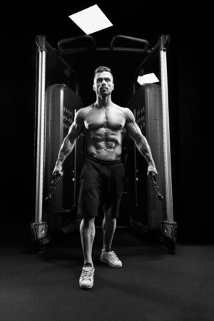 Front view of muscular shirtless bodybuilder doing low cable crossover exercise. Monochrome portrait of man with perfect body training chest in gym in dark atmosphere. Concept of bodybuilding.