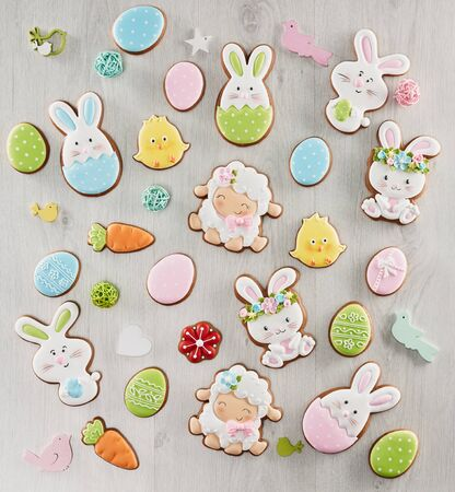 From above view of colorful ginger glazed cookies isolated on white wooden background. Close up of homemade lovely delicious pastry in shape of easter animals, eggs, flowers and carrots.