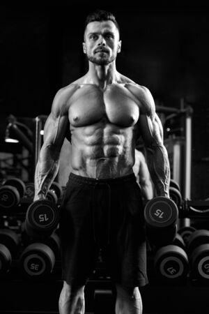 Monochrome portrait of shirtless male bodybuilder holding dumbbells in arms. Front view of caucasian sportsman with perfect muscular body posing in gym in dark atmosphere. Concept of bodybuilding.