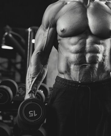 Front crop of shirtless incognito male bodybuilder holding dumbbell in arm. Black and white close up of sportsman with perfect muscular body posing in gym in dark atmosphere. Concept of bodybuilding.