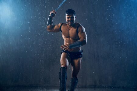 Front view of angry screaming wet roman gladiator holding blade. Muscular fearless shirtless warrior in armor running during attack in rainy bad weather, dark atmosphere. Concept of ancient warrior.