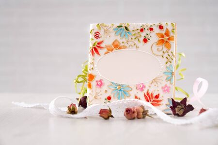 Front view of big white glazed square cookie painted with beautiful flowers. Willow branch, dried flowers and ribbons isolated on white background. Cute homemade pastry.