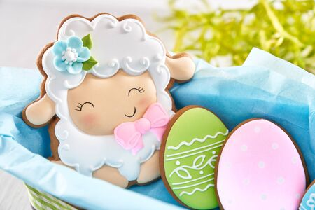 Close up of glazed cookies in shape of lovely sheep and two eggs lying in box with blue napkin isolated on white background. Cute homemade pastry. Spring and easter holidays concept.