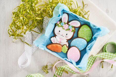 From above view of glazed cookies in shape of lovely bunnies, three eggs and carrot lying in box with blue napkin, ribbons isolated on white background. Spring and easter holidays concept.