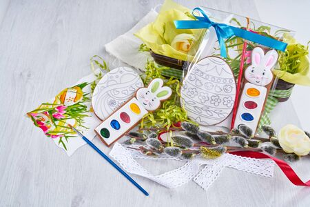 From above view of gift painting set for coloring easter eggs, isolated on wooden table. Watercolor paints near napkin, box with flowers, willow branch and brush. Spring and easter holidays concept.