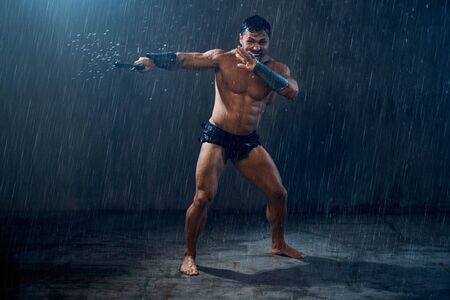 Motion of angry screaming wet roman gladiator swinging sword. Muscular shirtless spartan with agressive facial expression attacking in rainy bad weather. Concept of ancient warrior.