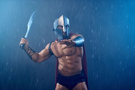 Front view of wet roman gladiator in iron helmet and red cloak brandishing sword. Muscular shirtless spartan in armor during fight in rainy bad weather. Concept of anciet warrior, sparta.