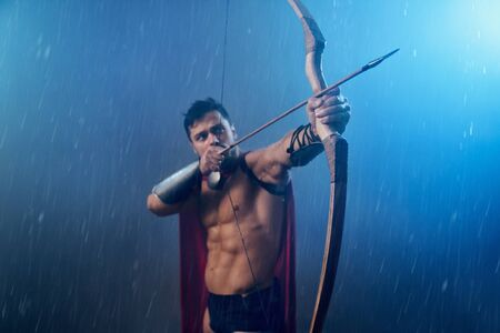 Front view of muscular spartan wearing red cloak, pointing up with wooden bow and arrow. Selective focus of weapon in arms of wet handsome man in historical outfit posing in bad rainy weather. 写真素材