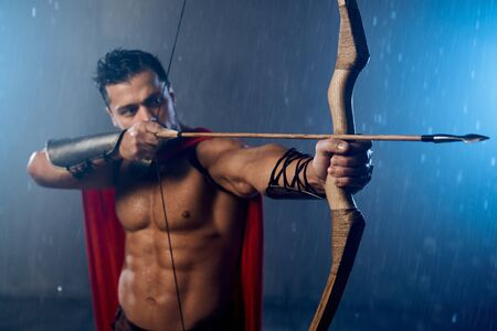 Front view of muscular mature spartan wearing red cloak, shooting from bow with arrows while raining. Selective focus of weapon in arms of wet handsome man in historical outfit posing in bad weather.