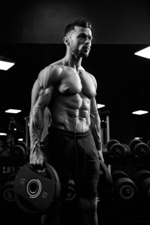 Side view of shirtless tensed male bodybuilder holding weights in arms. Monochrome portrait of caucasian sportsman with perfect muscular body posing in gym in dark atmosphere. Concept of bodybuilding.