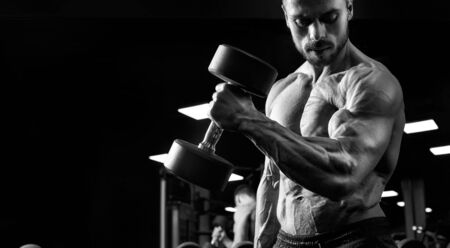 Black and white crop of shirtless male bodybuilder training biceps with dumbbell. Close up of sportsman with perfect tensed muscular body posing in gym in dark atmosphere. Concept of bodybuilding.
