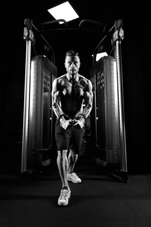 From below view of muscular shirtless bodybuilder training chest in gym in dark atmosphere. Monochrome portrait of man with perfect body doing high cable crossover exercise. Concept of bodybuilding.