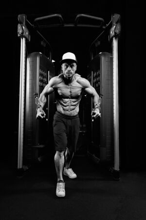 Front view of muscular shirtless male bodybuilder training chest in gym in dark atmosphere. Monochrome portrait of man with perfect body doing high cable crossover exercise. Concept of bodybuilding.