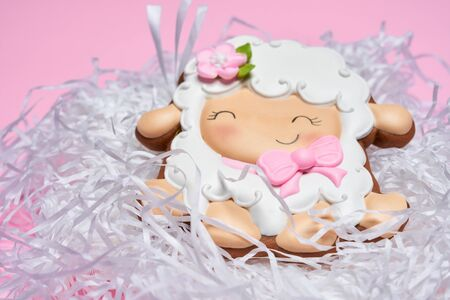 From above view of glazed cookie in shape of lovely smiling sheep lying in white nest isolated on pink background. Close up of cute pastry. Spring and easter holidays concept.