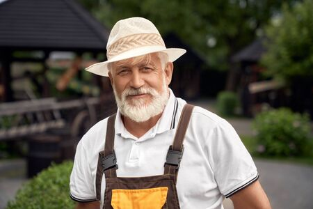 Portrait of positive senior man with grey beard wearing uniform and summer hat. Selective focus of eldery worker posing in garden near gazebos, looking at camera. Concept of gardening.