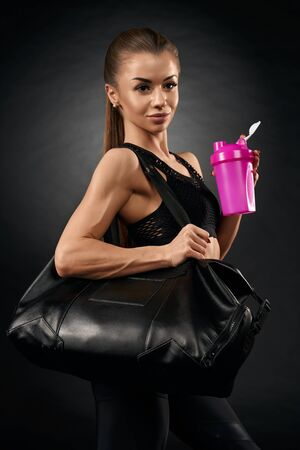 Young attractive fit woman posing with sport bag and holding pink shaker with water, isolated on black. Portrait of pretty female with ponytail in black sportswear going home after hard training.