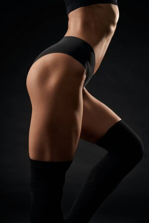 Crop of sexy incognito female model wearing black underwear and knee socks standing with leg bent, isolated on black. Side view of fit woman with perfect muscular buttocks and long hair posing.