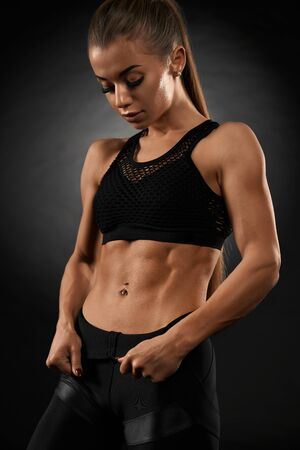 Close up of muscular woman holding leggings and showing tensed abs. Isolated portrait of pumped fitnesswoman in black sportswear posing on black studio background. Concept of sport, fitness. 写真素材
