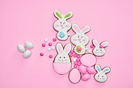From above view of big and small peanut chocolate balls in crispy sugar shell isolated on pink background. Easter ginger glazed cookies in shape of bunnies and eggs. Concept of easter holidays.
