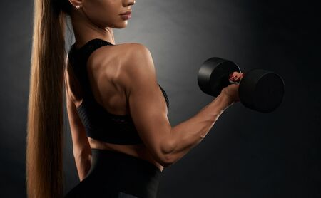 Side view of muscular incognito woman trining with dumbbells. Isolated crop of pumped fitnesswoman in black sportswear posing on black studio background. Concept of sport, fitness.