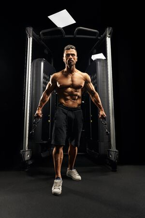Front view of muscular shirtless bodybuilder doing low cable crossover exercise. Portrait of tensed man with perfect body training chest in gym in dark atmosphere. Concept of bodybuilding.
