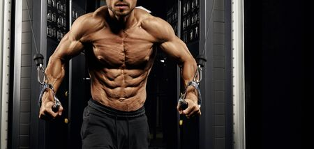 Front view of muscular shirtless male bodybuilder training chest in gym in dark atmosphere. Crop of incognito man with perfect body doing high cable crossover exercise. Concept of sport, bodybuilding.