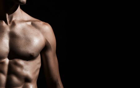 Unrecognizable shirtless fit bodybuilder showing powerful abs. Isolated crop of naked incognito holding posing and looking away on black studio background. Concept of bodybuilding, strength.